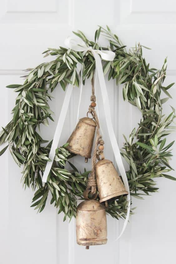 DIY farmhosue christmas decor. Wreaths with greenry and bells and ribbon.