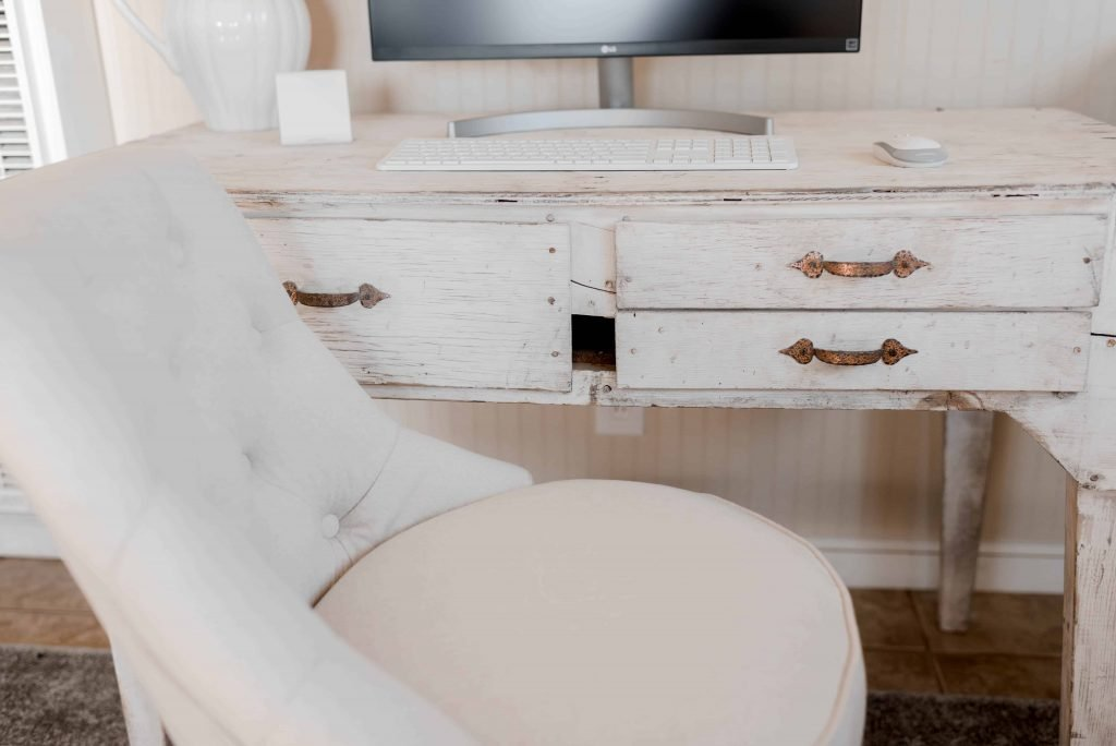 white antique wood desk in office with tufted natural linen chair