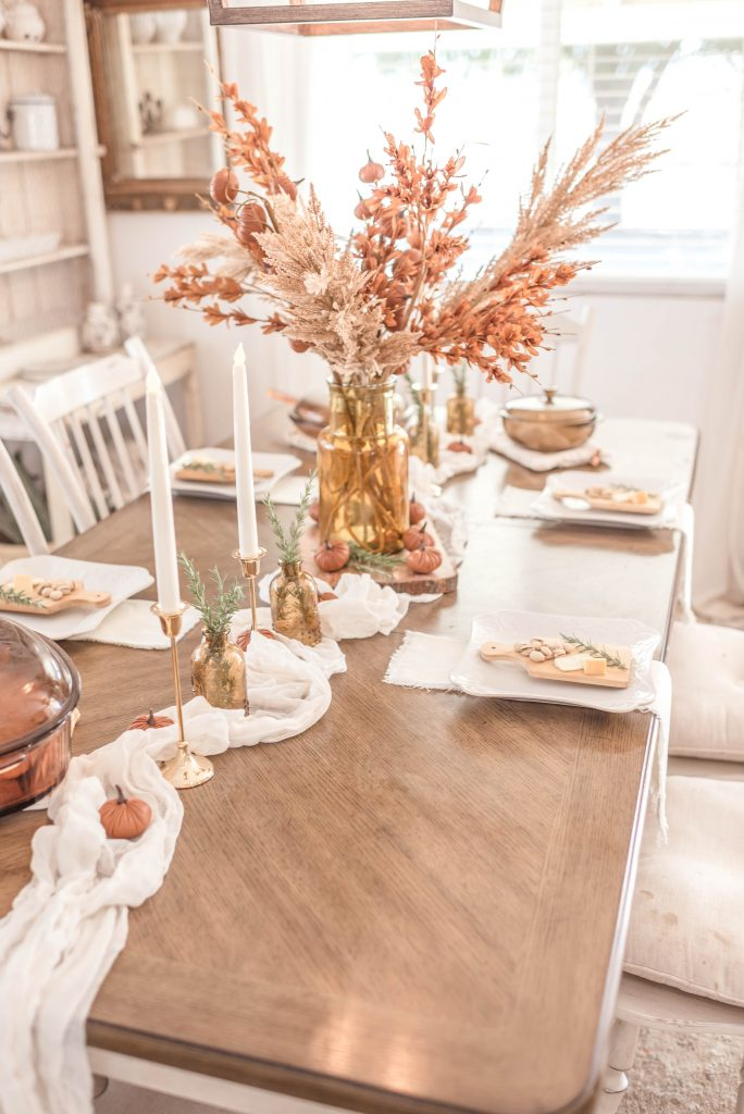 brown and cream fall tablescape with leather pumpkins